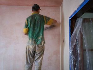 A plaster veneer wall being troweled smooth.