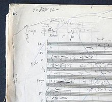 A piece of paper from a musical manuscript, covered in musical notation, accompanying annotations, lines etc