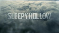 "The title ""Sleepy Hollow"" is written over a town shrouded by clouds."