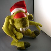 A green plush toy of a Vortigaunt sits against a gray wall. The toy is wearing a Santa Claus hat, leaving only the dominant red eye visible
