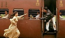 A woman in a dress runs to catch a train while a man is waiting with his hand out to help her