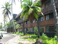 A building of the Coco Palms Resort with numerous rooms near the lobby.