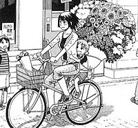A section of a page from the manga. Two girls ride a bike, with the older one steering and the other clinging to her from behind; the younger one has an enormous bundle of various flowers larger than her strapped to her back. In the background, a girl stares at them.