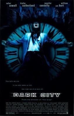 "A black poster. Above reads the lines: ""Rufus Sewell"", ""Kiefer Sutherland"", ""Jennifer Connelly"", ""and William Hurt"". In the center, against a black background, a man wearing a blue jacket is rested against an upright clock with Roman numerals as big as him; the setup cast in a blue tint. His arms are outspread, and his head is tilted back with his mouth agape. Behind the man and the clock is a dark city skyline. Below them is the tagline, ""They built the city to see what makes us tick. Last night one of us went off."" Below the tagline is the film title, ""Dark City""."