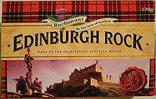"A box with a red tartan background, and image of Edinburgh Castle and in large letters across the middle, ""Edinburgh Rock""."