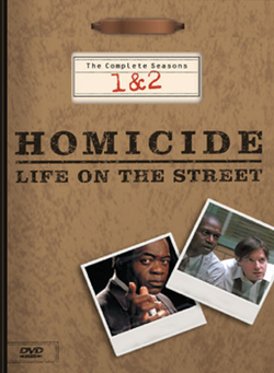 "A DVD box-set cover with a background resembling a brown file folder, including a metal clip at the top. The words ""Homicide: Life on the Street"" are printed in the middle of the cover, with the words ""The Complete Seasons 1 & 2"" above it. Underneath the words are two images resembling photographs, one with a man wearing a suit jacket looking straight forward and pointing with his index finger, and the other of two men wearing dress shirts leaning forward and looking sideways."