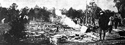 =A photograph of ashes from a burned building with several people standing nearby and trees in the distance