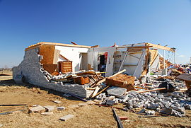 The remains of a home, now mostly a pile of rubble; part of the structure remains intact.