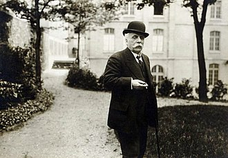 elderly man in a garden. He has a large white moustache, is holding a lighted cigarette, and is wearing a bowler hat