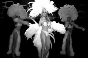 I Stay in Love - In the image, Carey is seen dressed in white garments and large feathers. She is featured as a dancer in Las Vegas, and is where she discovers her ex-lover has moved on.