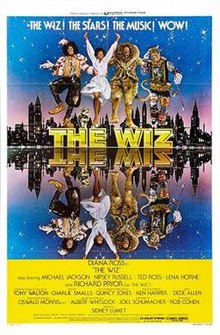 "Four characters from the film dancing on top of a logo ""THE WIZ"". A city s以除kyline just after dusk is behind them, and the entire scene is mirrored in water before them. The people are Dorothy, the Scarecrow, the Tin Woodman, and the Lion."