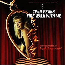 "A black-and white chevron floor and red curtains are in the background. In the front of the cover is a burning half of a heart-shaped necklace pendant which depicts a smiling young woman with light skin and blonde hair. The phrases ""Twin Peaks: Fire Walk With Me"" is placed upon this in white bold writing, while ""Music Composed by Angelo Badalamenti"" appears in smaller and thinner red writing."