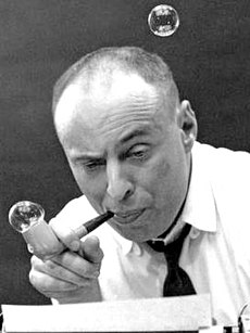 A black-and-white photo of a bald middle-aged man, blowing bubbles from a bubble pipe