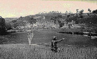 Battle of San Juan Hill - U. S. Army photo taken near the base of Kettle Hill about July 4, 1898. The soldier is pointing at the top of Kettle Hill. In the background are the block houses on San Juan Hill and the American encampment.