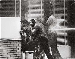 Three black high school students, two boys and a girl, facing into a storefront window to avoid being hurt by a water cannon Blasting one boy at his back; all three are dripping with water