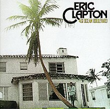 A house is shown along with a palm tree, on the right Eric Clapton holds his hands smiling, above him is the title and logo along with some trees