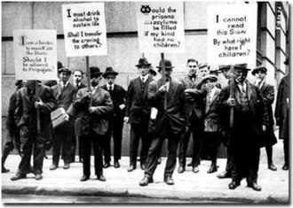 "Eugenics in the United States - Eugenics supporters hold signs criticizing various ""genetically inferior"" groups. Wall Street, New York, c. 1915."