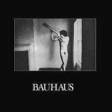 "The album cover has a black background with a square in the middle featuring a black-and-white image of a naked man posing with a metal object. Below this is captioned ""Bauhaus"" in white text."