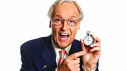 Image shows Nicholas Parsons smiling whilst holding a stopwatch in his left hand and pointing to the watch with his right hand