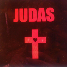 "The word ""Judas"" is written in capital red letters on a dark brown background. Below is a red cross with a black heart in the middle."