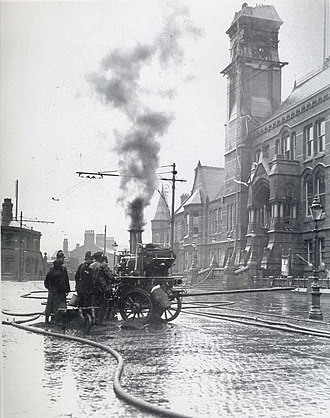 Fire appliances in the United Kingdom - A steam pump truck in use in 1913, St Helens enabling fire-fighters to reach the burning clock tower. The limber for attaching to a horse team is visible stretching to the right.