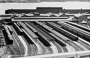 Black & white picture showing station facility with passenger cars. Hudson river visible behind the station.