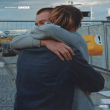 Two members of Brockhampton (JOBA & Weston Freas) hugging each other on the street.