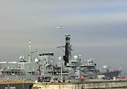 A modern Royal Navy destroyer blends into the skyline while docked