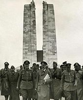 A group of men dressed in Nazi German soldier, front and centre is Adolf Hitler, June 1940. The twin pylons of the memorial are clearly displayed in the background.
