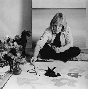 Maija Isola - At work, sitting cross-legged, paintbrush and paintpot in hand