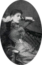 portrait of young white woman with dark hair, leaning back in a chair