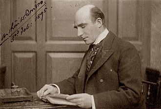 photograph of middle-aged white man, bald, clean-shaven, sitting at writing-desk