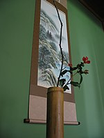 A chabana flower arrangement in front of a hanging scroll