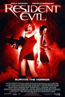 "A black and red picture shows Alice standing back to back with Rain. Alice is holding a machine gun and wearing a red dress, cutaway showing a skirt. The tagline below reads ""Survive the horror""."