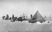 Six men are working with sledges and camping equipment, close to a pointed tent pitched on a snowy surface. Nearby, upright skis have been parked in the snow