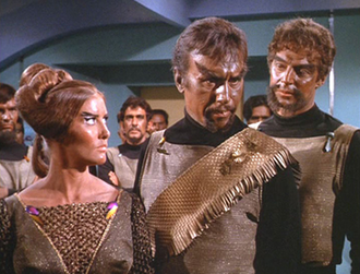 "Klingon - Two Klingon men and a Klingon woman as they appear in the Star Trek: The Original Series episode ""Day of the Dove"". The bronzed skin, facial hair, lack of ridged foreheads, and simple costumes are typical of The Original Series."