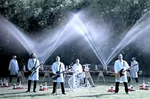 "Weezer plays in the foreground while Fritz Grobe and Stephan Voltz set off Diet Coke and Mentos eruptions behind them in the ""Pork and Beans"" music video. Three members of the band are playing guitar while the other (Pat Wilson) is playing the drums. They are all wearing white tops and black pants."