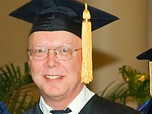 Profile shot of a bespectacled man in his early fifties, wearing a mortarboard with a yellow tassel
