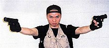 Seung-Hui Cho, standing and holding a gun in each hand; wearing a black baseball cap turned backwards, black gloves, and a vest.