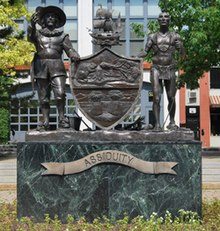 A bronze statue is seen that depicts most of the details of the coat of arms shown in the infobox image. The men and the sloop are three-dimensional representations of the respective components in the shield. The shield itself is relief work.