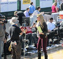 Erin Andrews ist aus der Ferne mit einem Mikrofon zu sehen, als sie mit einer Kamera spricht