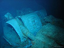 The mangled wreck of a naval gun turret. The photograph has a blue tinge, as it was taken in deep water.