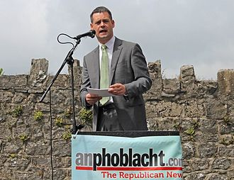 An Phoblacht - Pearse Doherty TD delivers the main oration at the annual Wolfe Tone Commemoration in Bodenstown, 2013. The podium carries a banner advertising An Phoblacht to the audience