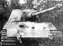 A head-on view of a large tank with a flat faced turret. Its sloped bow armor is scarred with several fist-sized dents, and there is a fist-sized hole in the front of the turret