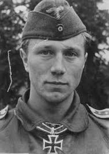 The head and shoulders of a young man, shown from the front. He wears a field cap and a military leather pilot jacket, with an Iron Cross displayed at the front of his collar. His facial expression is a determined and confident smile; his eyes are looking into the camera.