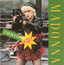 "A young woman with short cropped blond hair is pointing towards somebody while holding a gun. She is wearing a red skirt and black jacket and gloves. On her left, the word ""Madonna"" is written in green and on the center of the image, the word ""Causing a Commotion"" is written in capitals."