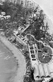Black and white aerial photograph of a small island with unroofed buildings, trees stripped of their leaves and branches, and debris scattered over the ground and beach.