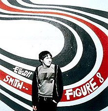 "A man (Elliott Smith), rendered in black-and-white, stands in front of a wall with a white background and four big swirly lines of paint forming an 'S' shape behind him; the first two are black, the third is red, and the last is black. ""Elliott Smith ••"" and ""Figure 8"" are written in white text on the swirls to the left and right sides of the man, respectively."