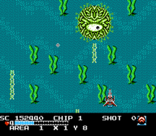 A red spaceship at the bottom of the picture, behind a blue background that resembles an ocean floor, dodges projectiles from the enemy boss, a round, green, amoeba-like creature, on the top of the picture.