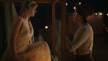 "A scene in the ""Willow"" music video, where Swift is trapped inside a glass box, unable to join her love interest. Taylor Swift - Willow (music video screenshot).png"